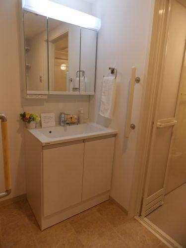ゆったり脱衣室、ワイド鏡の洗面台付。段差もなく、手すり、緊急通報ボタン完備